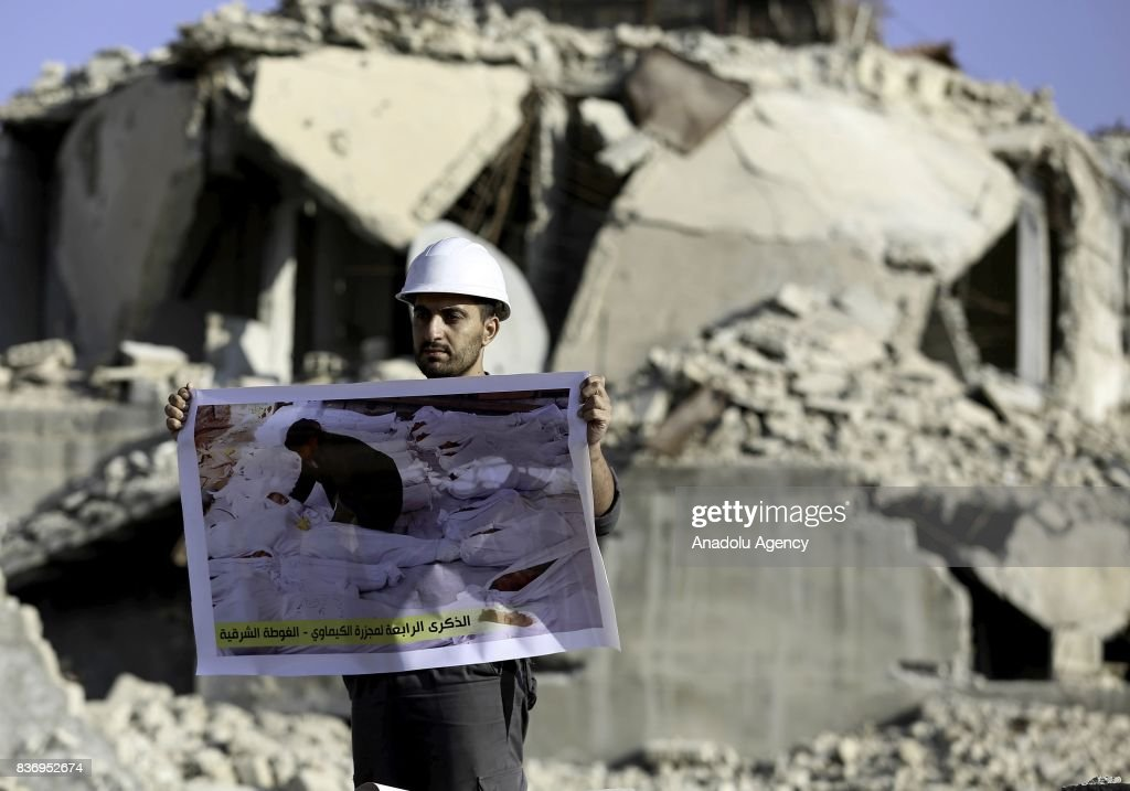 A man, member of Syrian civil defense organization, White Helmets holds a photo of a person who lost his life in chemical attack that in the Eastern Ghouta region of Damascus, Syria on August 22, 2017. It is the 4th anniversary of chemical weapons attack near countrysides of Zamalka that Assad Regime's forces carried out.