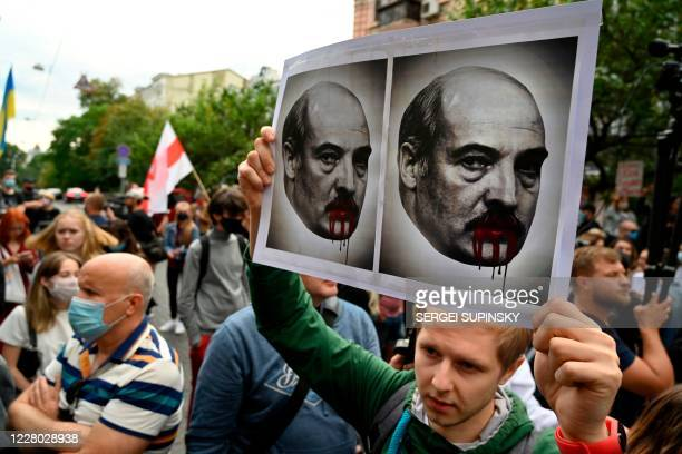 Man, member of the Belarus diaspora holds a placard depicting Alexander Lukashenko with blood on his mouth and moustache as he with others take part...