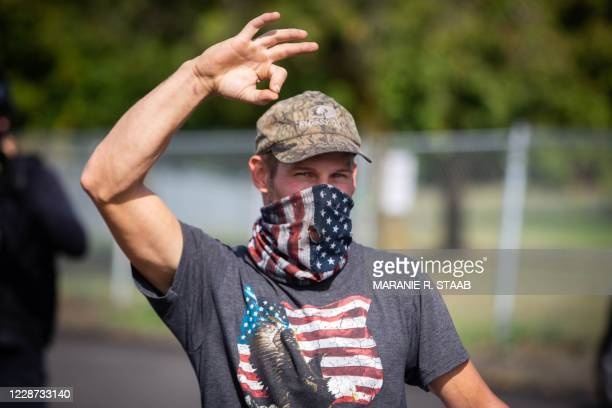 Man, member of the Proud Boys and other similar groups, gestures the OK sign that is now seen as a symbol of white supremacy, as hundreds gathered to...