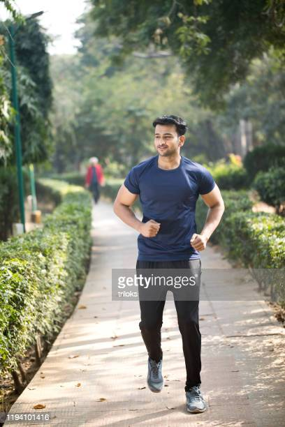 man men jogging at park - sportswear stock pictures, royalty-free photos & images