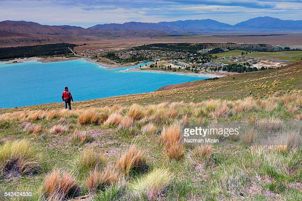 A man mesmerized by the beautiful color of Lake Tekapo.