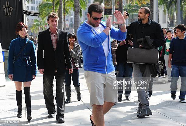 A man mimics a no pictures gesture as he walks in front of actors Jack Minor and Julie Le followed by a few other actors pretending to be fans or...