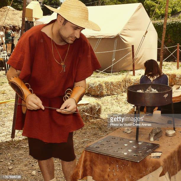 man minting coins dressed in roman era clothes for the arde lucus annual festival - victor ovies fotografías e imágenes de stock