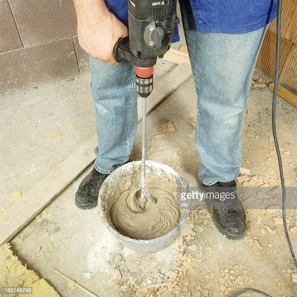 Man mixing concrete with drill