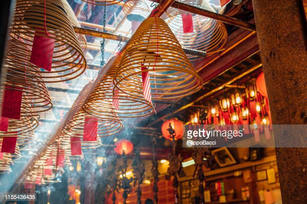 man mo temple in hong kong with sun beams and incense - incense stock photos and pictures