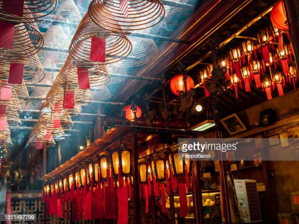 man mo temple in hong kong with sun beams and incense - incense coils stock pictures, royalty-free photos & images