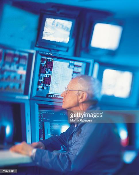 man monitoring computer screens - monty rakusen stock pictures, royalty-free photos & images