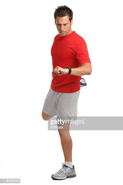 Mann, die Kontrolle der Herzfrequenz und Dehnübungen vor dem Joggen