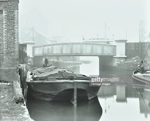 Man mooring a barge by a river bank Poplar London 1905 Barge on still water a singledecker tram passes over the bridge
