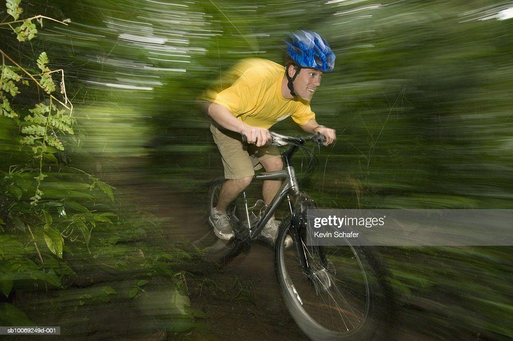 Man mountain biking in forest, (blurred motion) : Stockfoto