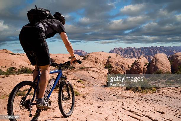 man mountain biking on the slickrock trail in moab, utah - moab utah stock photos and pictures