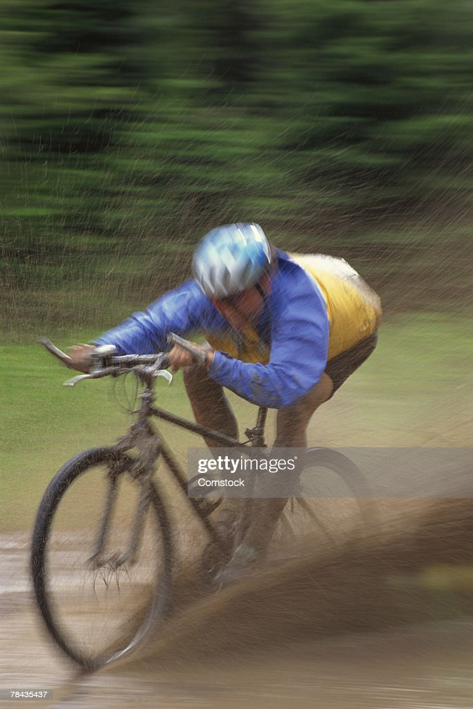 Man mountain biking through mud : Stockfoto