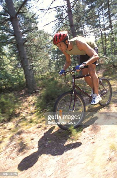 Man mountain biking through trail