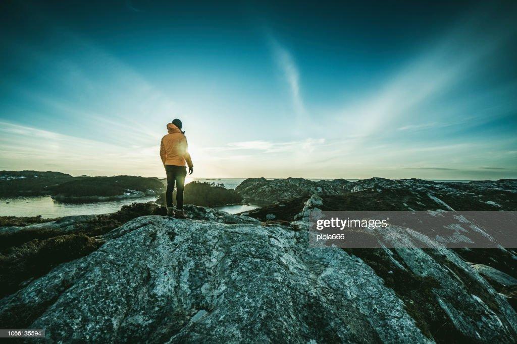 Bergwandelen van de man door een fjord in Noorwegen : Stockfoto