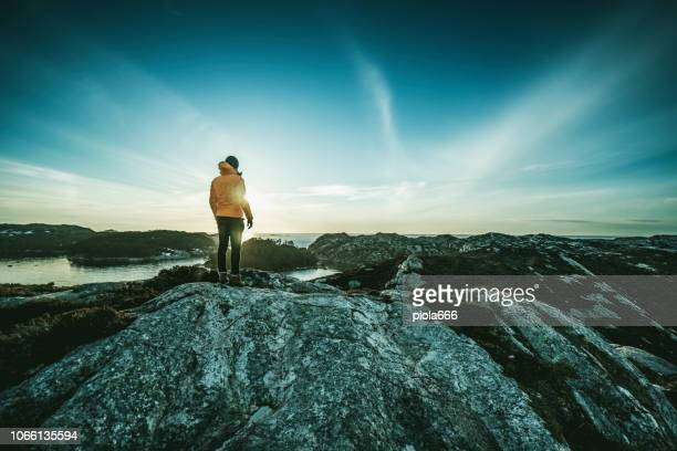 man mountain hiking by a fjord in norway - mountain stock pictures, royalty-free photos & images