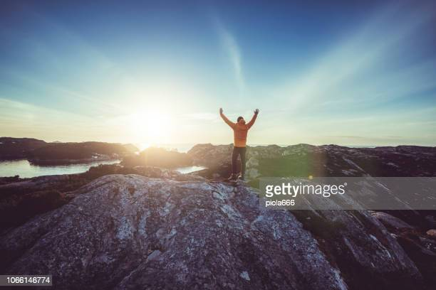 man mountain hiking by a fjord in norway - hordaland county stock pictures, royalty-free photos & images
