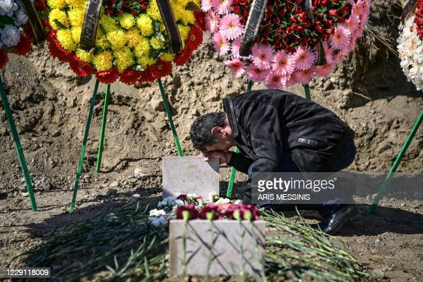 Man mourns above a grave of a fellow fighter in Stepanakert during fighting over the breakaway region of Nagorno-Karabakh on October 17, 2020. -...