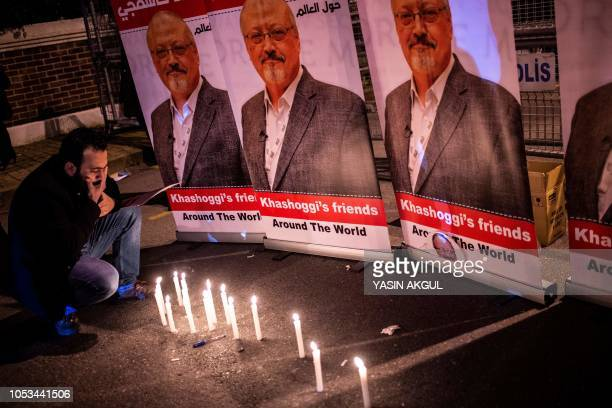 A man mourns by a makeshifts memorial made of candles and posters picturing Saudi journalist Jamal Khashoggi during a gathering outside the Saudi...