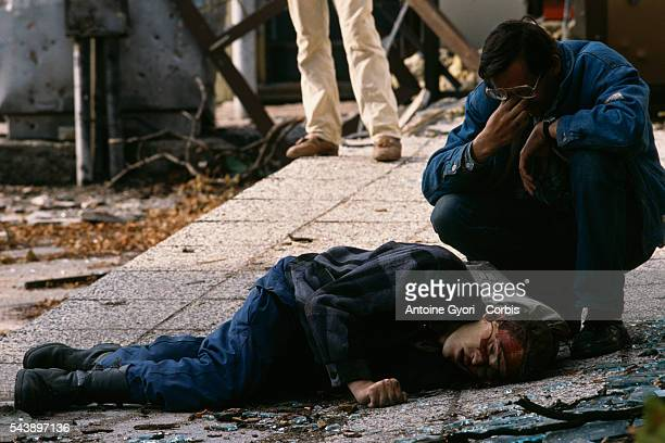 Man mourns next to the body of a civilian victim of the siege of Sarajevo who was killed by a sniper during the Yugoslavian Civil War. The siege of...