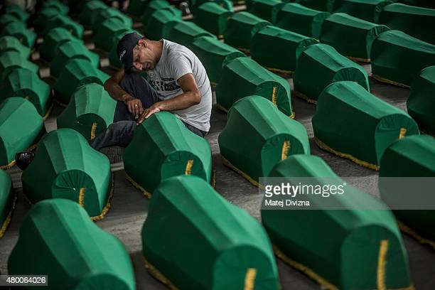 A man mourns over a coffin among 136 coffins of victims of the 1995 Srebrenica massacre in the hall at the Potocari cemetery and memorial near...