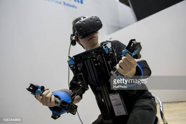 A man moves a robot using virtual reality during the Japan Robot Week 2018 at Tokyo Big Sight on October 17 2018 in Tokyo Japan At this biennial...