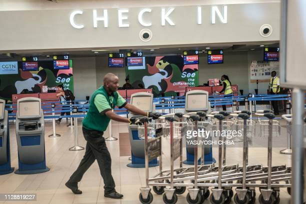 A man moves carts in front of unmanned Kenya Airways's checking counters at the departure terminal during a strike by airline workers at the Jomo...