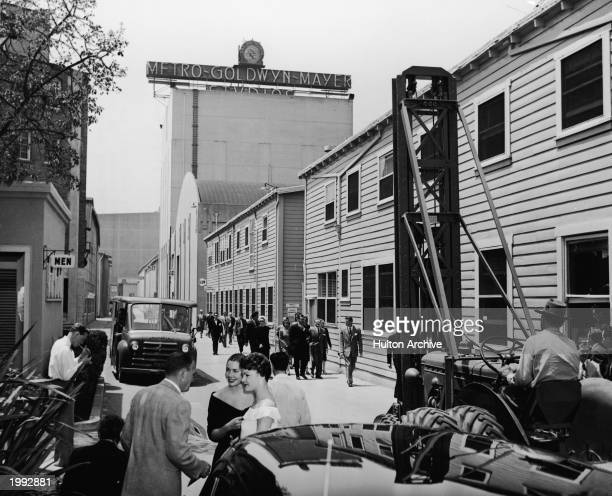 A man moves machinery and sets as groups of people walk down the main thoroughfare of MGM Studios Hollywood California circa 1945
