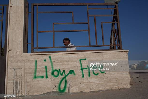 A man moves to close a gate of a cemetery on August 28 2011 in Tripoli Libya Heavy fighting continues in Gaddafi's home city of Sirte between...