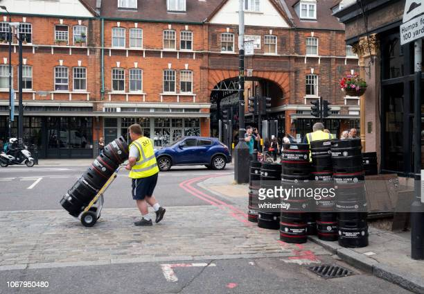 man moving beer barrels in commercial street near spitalfields in london - the brewery london stock photos and pictures
