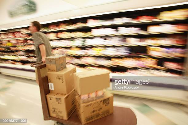 Man moving boxes in grocery store (blurred motion), rear view