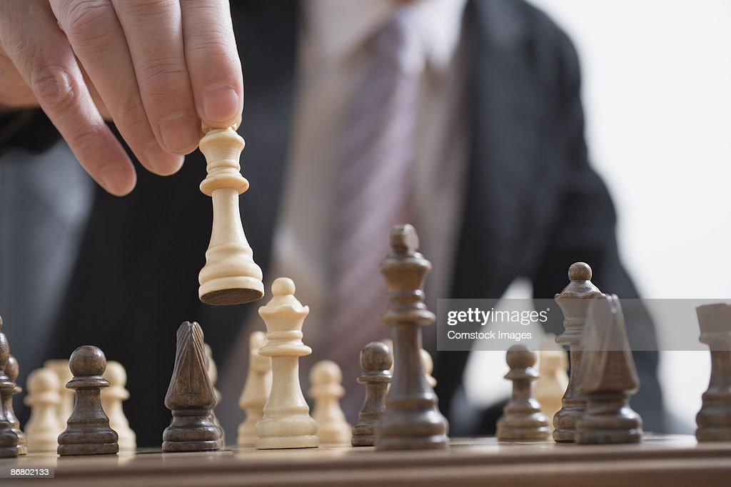 Man moving chess pieces : Stock Photo