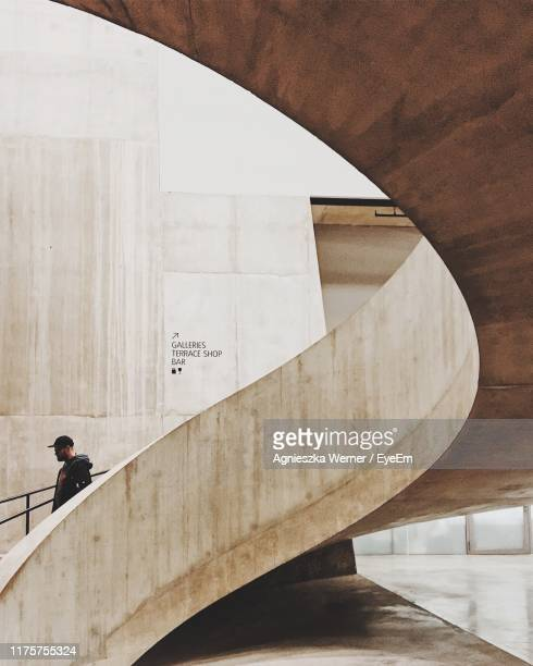 man moving down on spiral staircase against wall - architecture stock pictures, royalty-free photos & images