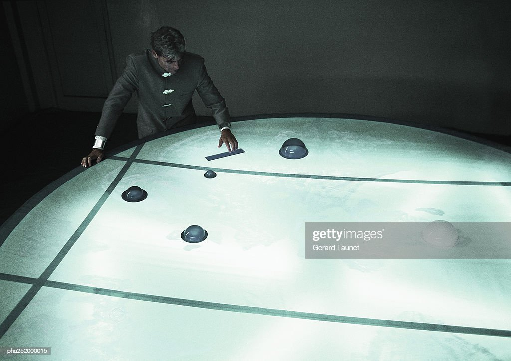 Man moving object on round table, high angle view : Stockfoto