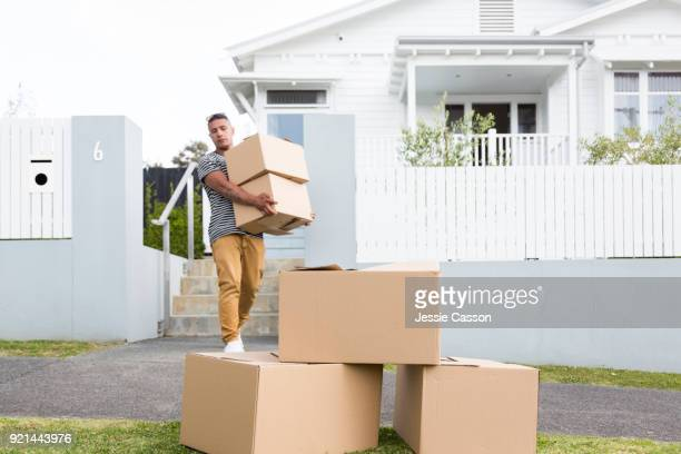 Man moving packing boxes out of home