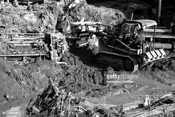 A man moving the rubbles on a bulldozer after a flood in the district of Biella Italy 1968