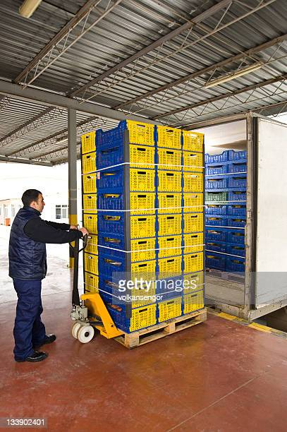 Man moving warehouse shipment on metal trolley
