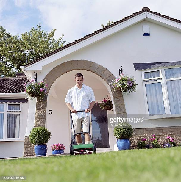 Man mowing front lawn, ground view