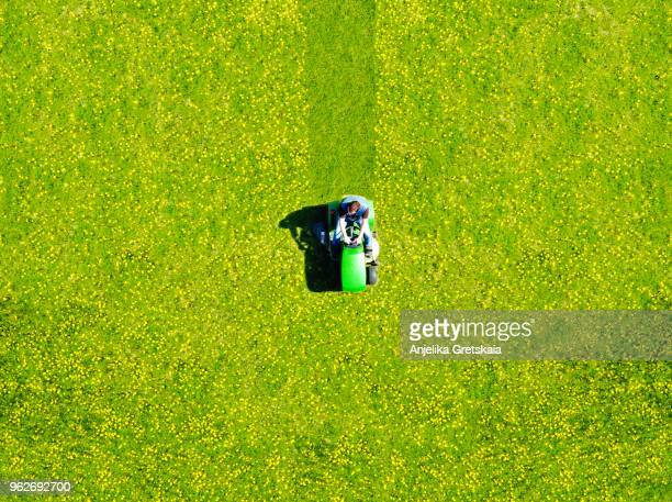 man mowing green field of dandelions, aerial view - lawn stock pictures, royalty-free photos & images