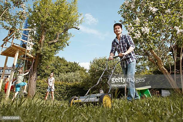 Man mowing lawn in garden with family in background