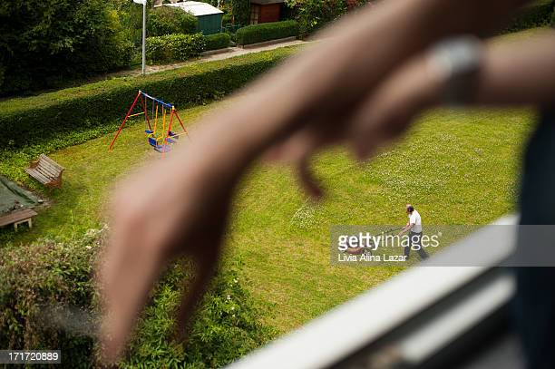 CONTENT] Man mowing lawn perspective hand with a cigarette out of focus garden bench children cradle