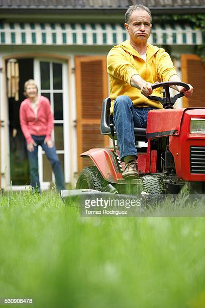 Man mowing lawn, wife in background