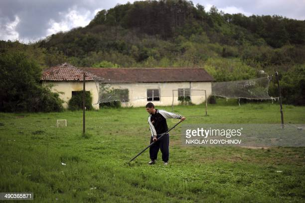A man mows the lawn of a playground in the village of Drazhintsi some 180 km north from Bulgarian capital Sofia on April 29 2014 In northwest...