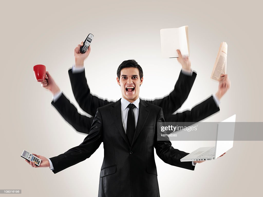 A man multitasking with several arms holding items : Stock Photo