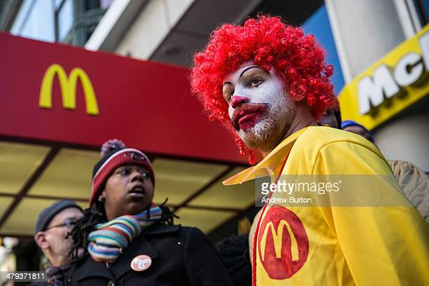 A man named Ben who chose not to give his last name dressed as the McDonald's mascot Ronald McDonald participates in a protest for higher wages for...