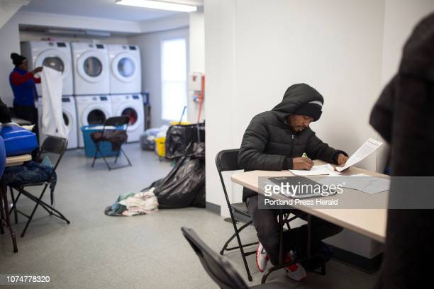 A man named Landu fills out paper work in the Family Shelter warming center on Thursday December 13 2018 Families who are seeking asylum spend their...