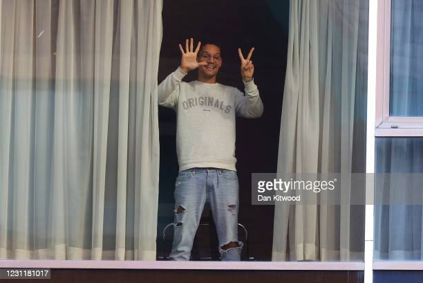 Man named Roger Goncalves gestures from his window towards reporters outside the Radison blu hotel after arriving at Heathrow airport, reportedly...