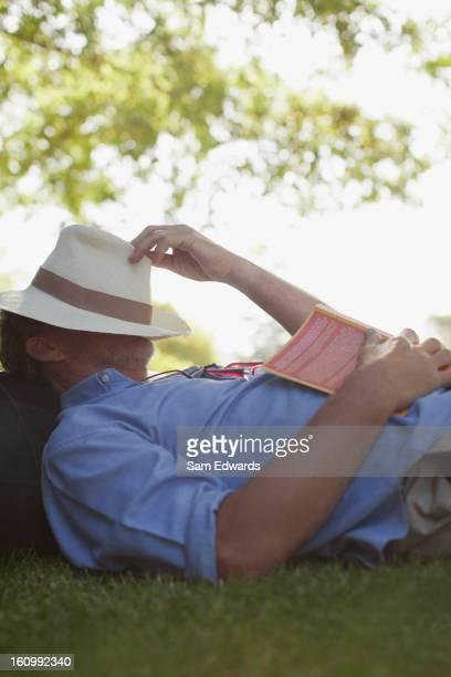 Mann Nickerchen auf Rasen mit Buch und Hut auf Gesicht
