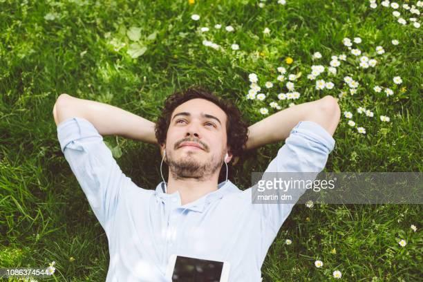uomo che sonnecchia nell'erba - gente serena foto e immagini stock