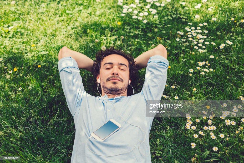 Homem dormindo na grama : Foto de stock
