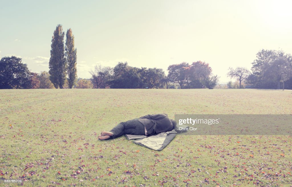 Man napping on coat in park field : Foto stock